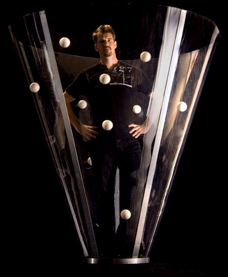Conic: Greg Keneddy juggling mulitple balls while standing in a large clear cone.